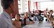 Schoolkids raising hand in classroom
