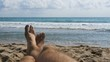 Legs of Men Lying on Beach near the Sea, POV. Slow Motion in 96 fps. Man lie on the sandy beach, overlooking the Sea. Young man relaxing on a resort.
