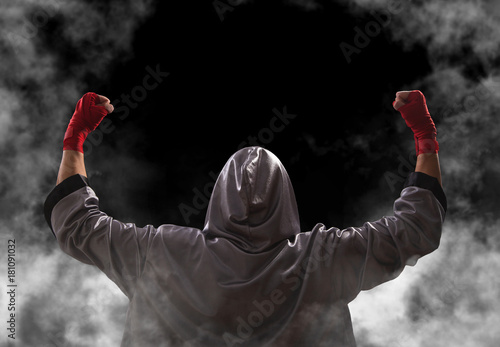 Female boxer with red boxing wraps wins the fight and bacame a champion Fototapeta