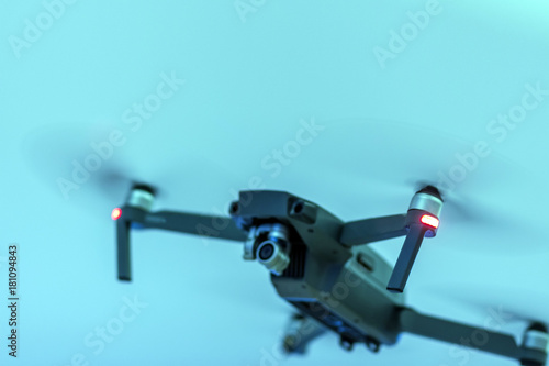 A blurry black unmanned radio-controlled drone on a blue background. Shallow depth of field.