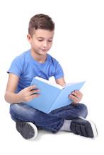 Cute Little Boy Reading Book O...