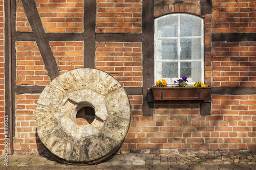 Fotoposter Molens Old millstone in front of half-timbered house
