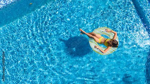 Obraz na płótnie Widok z lotu ptaka dziewczyna w pływackim basenie od above, dzieciak pływanie na nadmuchiwanym ringowym pączku i zabawę w wodzie na rodzinnym wakacje