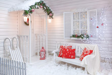 Winter Exterior Of A Country House With Christmas Decorations In The American Style. Snow-covered Courtyard With A Porch, Tree And Wooden Vintage Sleds.