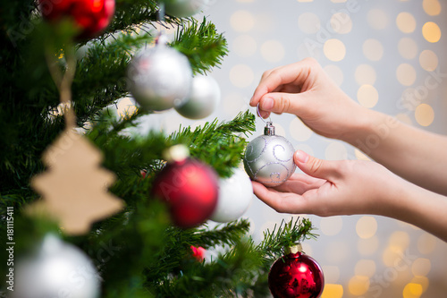 Fototapeta christmas background - close up of woman decorating christmas tree obraz