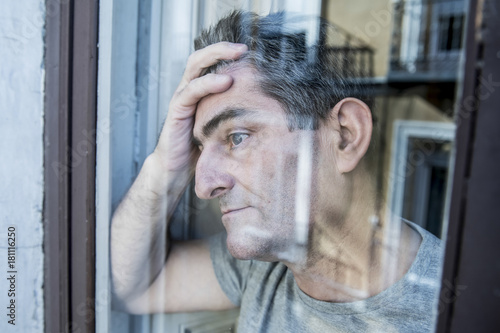 Fotografia  close up portrait of sad and depressed 40s man looking through w