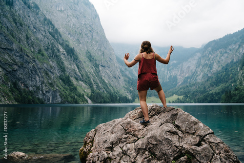 Poster Bergen Young woman standing on rock looking at beautiful and misty lake