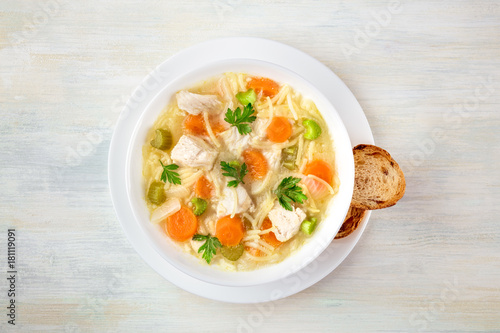 Fotografia Chicken soup with noodles, overhead photo with copyspace