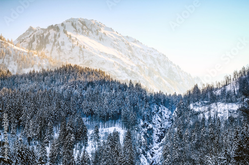 Fotobehang Bergen Sunrise in snowy winter mountains and woodland. Hintersteiner Tal, Allgau, Bavaria, Germany.