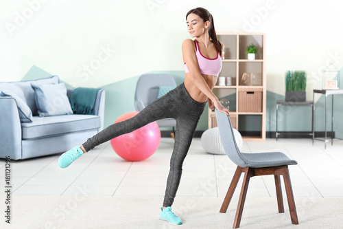 Montage in der Fensternische Gymnastik Beautiful young woman doing exercises with chair at home