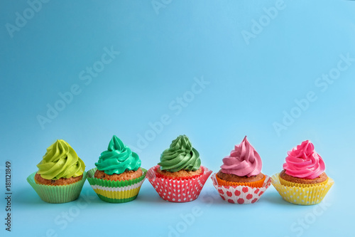 Photo  Tasty cupcakes on color background