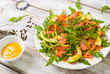 Salad with rocket salad \ arugula, avocado, grapefruit, red fish and mustard sauce on a white wooden background, top view