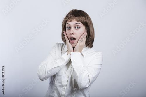 ragazza con capelli a caschetto e camicia bianca, guarda in macchina e si stupis Canvas Print