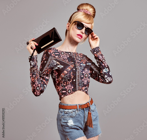 Fashion. Young Woman in Glamour Sunglasses, Sexy model Girl, cheeky Emotion. Stylish Hairstyle, Trendy Outfit. Blond with Glamour Handbag Clutch, fashion pose Wall mural