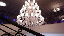 Luxury Large Crystal Chandelier Hanging In The Palace. Vintage Lighting Lamps With Light Bulbs And A Lot Of Pendants. The Rich Interior Of The Hall Of Ancient Ages.