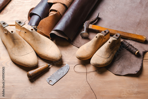 Leather in rolls, cobbler tools and shoe lasts in workshop Wallpaper Mural