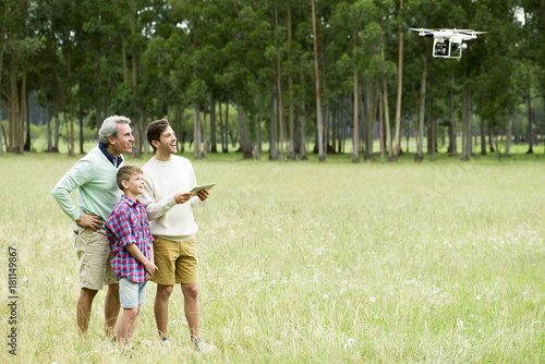 Man flying remote control drone in open field while older man and boy watch