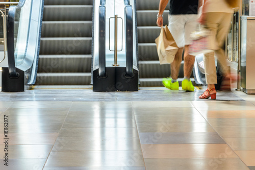 People Legs On Escalator Motion Blurred, Front View. Abstract Blur  Background Of Moving Staircase