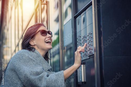 Happy woman using intercom at building entrance. Canvas-taulu