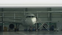 Roller Shutter Door And Plane In Hangar Background. Business Jet Airplane Is In Hangar. Private Corporate Jet Parked In A Hangar Facing Away From The Camera Towards The Doors In An Aviation