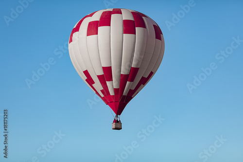 red white hot air balloon in the cloudless blue sky closeup