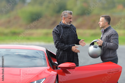 Fototapeta  race engineer talking with pilot about strategy near lamborghini