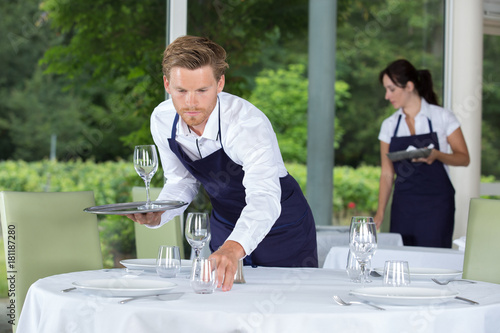 Leinwand Poster male waiter setting wedding table