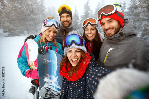 Poster Wintersporten winter, extreme sport and people concept - friends having fun on the snow and making selfie