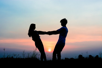 silhouette of romantic couple at the sunset time on meadow. Have a beauty pink and blue sky.