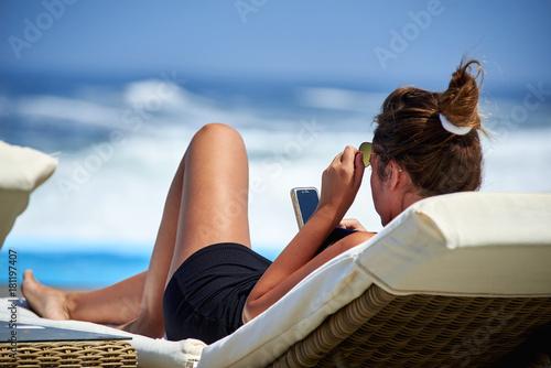 Fototapeta atractiva y joven mujer tomando sol y viendo el celular obraz na płótnie