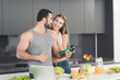 A man and a woman in the kitchen in the morning. A man will play with a green vegetable cocktail in his hands.