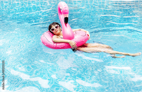 Foto op Aluminium Flamingo An Asian woman floating in the pool with inflatable floats