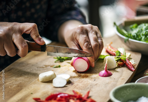 Hands using a knife chopping turnips