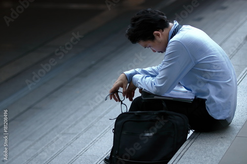 Fotografie, Tablou Frustrated stressed young Asian business man feeling strain or tried or disappointed at staircase