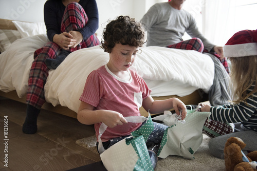 Photo Little kids unwrapping Christmas presents
