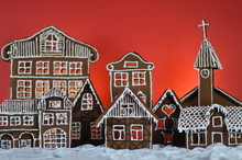 Home Made Gingerbread Village In Front Of Red Background On White Snowlike Velvet As Christmas Decoration