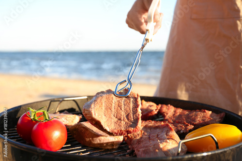 Man cooking steaks and vegetables on barbecue grill, outdoors