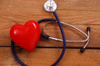 Red heart with a medical stethoscope, isolated on wooden background, selective focus