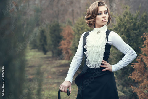 Photo Portrait of gorgeous young woman with elegant Victorian hairstyle wearing old-fashioned gown with jabot leaning on her cane and looking aside, misty autumn park on background
