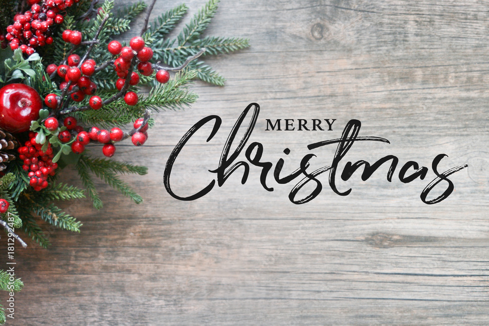 Fotografie, Obraz  Merry Christmas Text with Christmas Evergreen Branches and Berries in Corner Ove