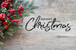 canvas print picture - Merry Christmas Text with Christmas Evergreen Branches and Berries in Corner Over Rustic Wooden Background