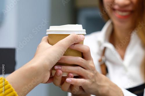 Plakat Młoda kobieta barista porcja bierze papierową filiżankę z uśmiechniętą twarzą w kawiarni, właściciela małego biznesu, jedzenia i napoju pojęcie, ludzie stylu życia