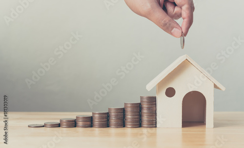 Fototapeta Property investment and house mortgage financial concept, Hand putting money coin stack with wooden house obraz