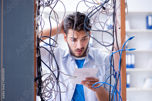 Fotografie, Obraz  Computer repairman working on repairing network in IT workshop