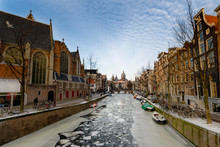 Amsterdam, Netherlands - February 2012. Boats Are Stuck As The Canals Of The Dutch Capital Freeze With Temperatures Below Zero. In Picture A Frozen Canal With Cracked Ice Near The Old Church.