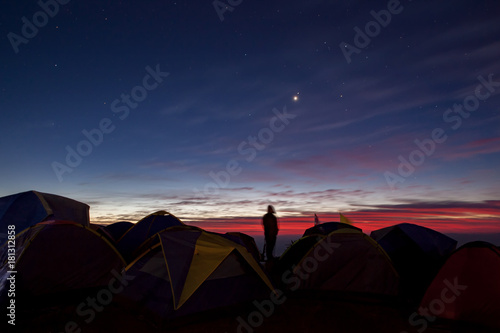Foto op Canvas Khaki camping man standing in camping area against beautiful colorful sun rising sky