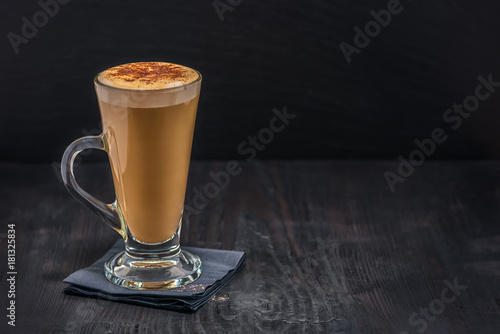 Obraz na plátně coffee latte in glass with froth of milk on black paper napkin over wooden table