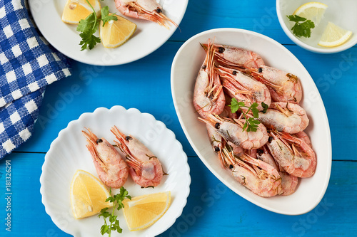 Prepared shrimps on white plate with parsley and slices of lemon Canvas Print