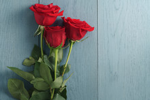Three Red Roses On Blue Wood T...