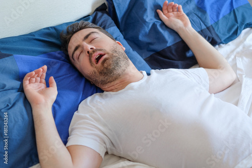 Photo Man in bed snoring and suffering for sleep apnea syndrome